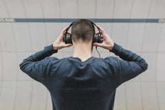 Guy listening to music and holding his headphones in