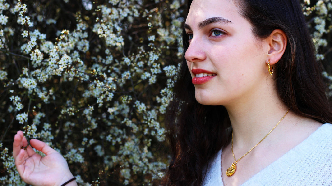 Female model shown wearing greenhouse gas earrings and Ammonite pendant from Ontogenie Science Jewelry