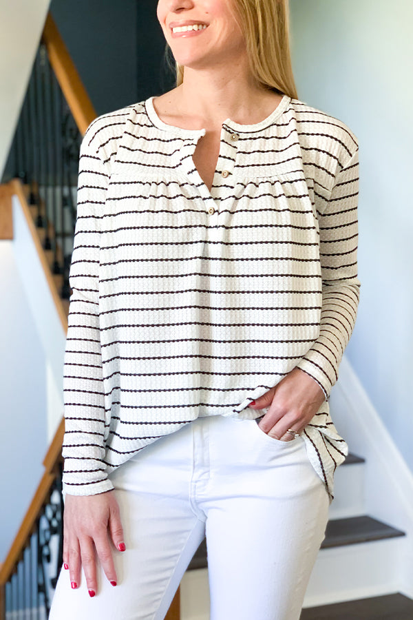 Look cute in our Striped Waffle Knit Top.  This long sleeve top features a cute white and black striped pattern, functional henley style buttons, relaxed body, and fitted sleeves through forearms.  Pair with our Waffle Knit Cardigan and jeans for the cutest, chic outfit.