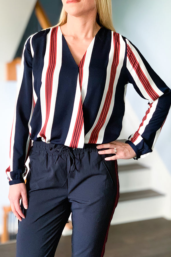 The Navy Stripe Long Sleeve Surplice Bodysuit is the perfect date night blouse. This bodysuit features v-neckline, button cuff sleeves, a keyhole back detail, and two snap closure. Beautiful navy blue, off-white and deep red stripes give an elegant touch to this soft, semi-sheer top.  Pair with a blazer and dress pants for a chic office outfit. Black Tape Surplice Bodysuit.