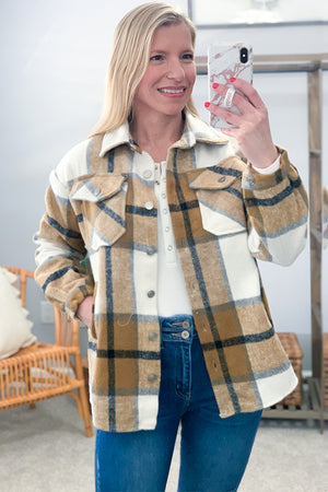 Our Camel Plaid Shacket is the perfect color combination for cooler days.  Featuring an off white, camel brown, and black big plaid print, medium weight fabric, collared neckline, side pockets, and button up detailing.  This is the perfect layering piece!  Throw over a basic tee and your favorite flares!