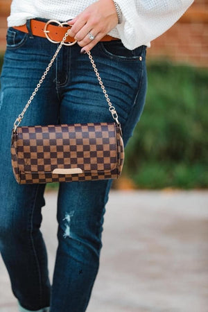We've got the cutest handbag for all your accessory needs!  The Checkered Crossbody Clutch in Brown features detachable shoulder and chain style straps, fold over closure, and interior open side pockets.  Wear as a crossbody or carry as a clutch.  Details  Brown Checkered Pattern Detachable Crossbody Strap Detachable Chain Strap Crossbody Purse Clutch Fold Over Closure Interior Open Side Pockets