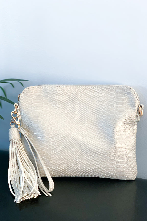 The Cluth Crossbody With Side Tassel Snake Pale Gray comes with an adjustable crossbody strap and a wristlet strap.  Cute tassel detail and a back zipper pocket to hold additional items.