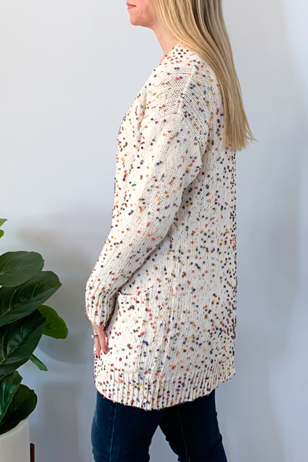 The Confetti Cardigan With Pockets is a must-have for a cozy weekend outfit.  Cute cream based knit with multicolored confetti make this cardigan easy to pair with almost any color basic tee.  This super cozy cardigan features an open front, long sleeves, and front pockets.  Pairs easily and effortlessly with a graphic tee, skinny jeans, and your favorite booties.  Pairs so cute with our Bright & Merry Long Sleeve Graphic Tee!