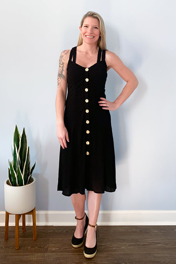 Looking for the cutest LBD? Then the Dex Black Midi Dress With Gold Buttons is exactly what you need!  This flattering dress will make you look and feel gorgeous! This midi dress features double strap criss cross detail, gold functional buttons down the front, and made with a crepe like fabric.  This dress is fully lined and perfect for pairing with a cute wedge sandal for an easy daytime outfit.  Also, this dress has a small amount of stretch to it.