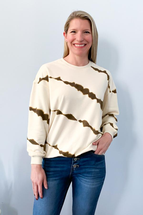 Black Tape Tie Dye Sweatshirt We're loving the vintage vibes of this Tie Dye Sweatshirt.  Cream and bronze colored tie dye print with a scoop neckline and drop shoulder.  This is a must have for a casual, cool outfit.  Perfect for pairing with skinny jeans and cute booties.