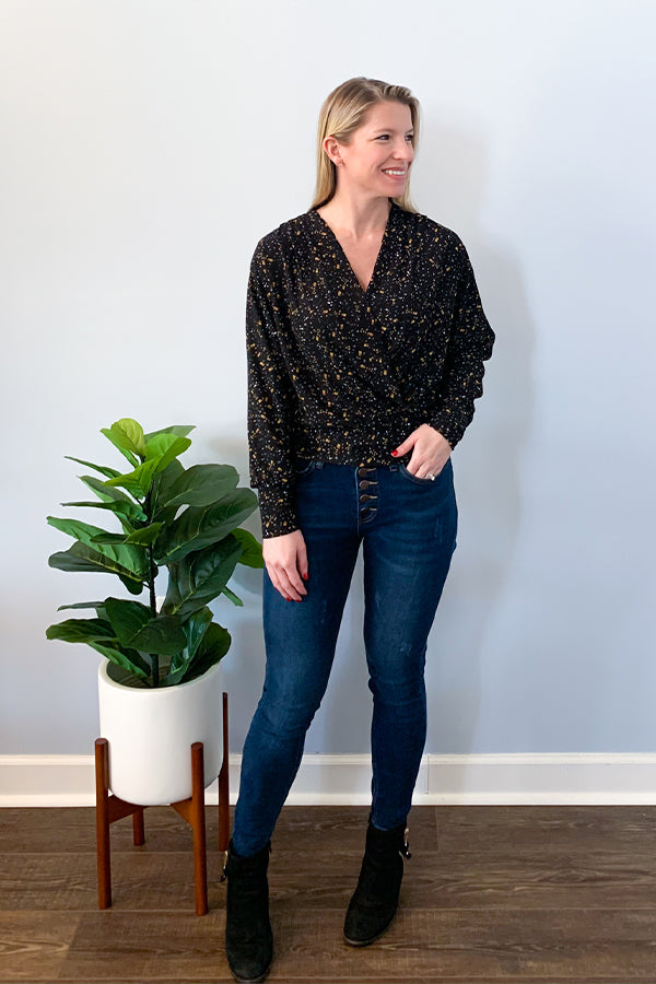 This beautiful Marigold Floral Print Blouse by Dex is the perfect date night blouse.  This wrap top features a banded hem, long sleeves, and is slightly cropped.  Black base with a beautiful marigold floral print.  This blouse is perfect for pairing with a cardigan for an office outfit or throwing under a faux leather jacket for a fun dinner outfit.