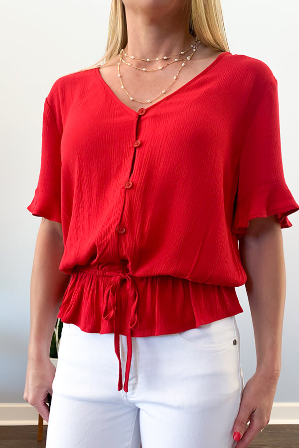 We love the feminine details in this beautiful blouse.  This drop waist blouse features a cinched tie waist, v-neckline, button front, and flirty ruffle sleeves.  This blouse is perfect for wearing casual with jeans and sneakers or dressing up with a pencil skirt and your favorite heels. Dex Red V-neck Ruffle Sleeve Blouse.