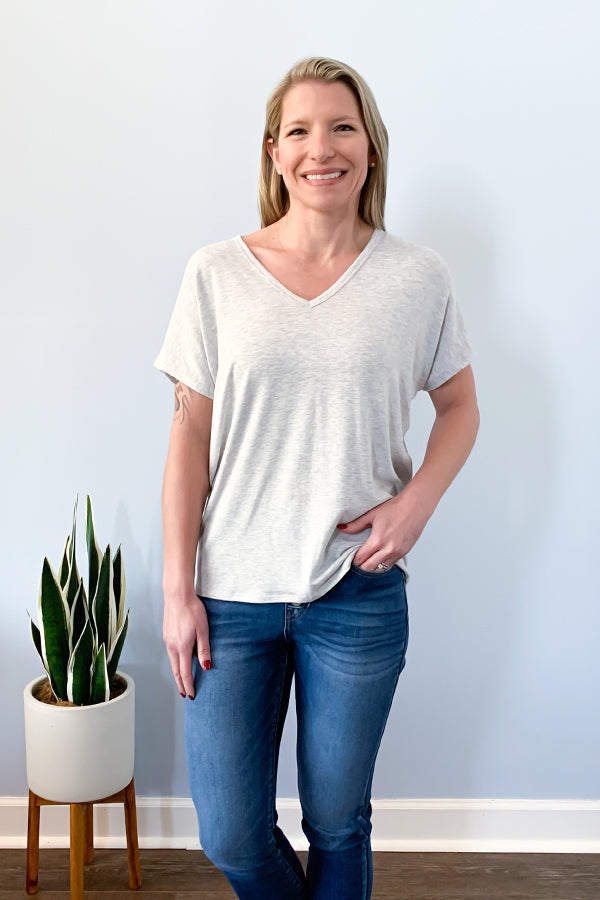 This super soft, heather grey top is so comfy you'll want to wear it every day!  Step up your basic tee game with our Grey Drape Open Back Tee by Dex.  Soft fabric v-neck tee featuring a drape open back with cross back detail.  Pair with jean shorts and sneakers for a casual weekend outfit.