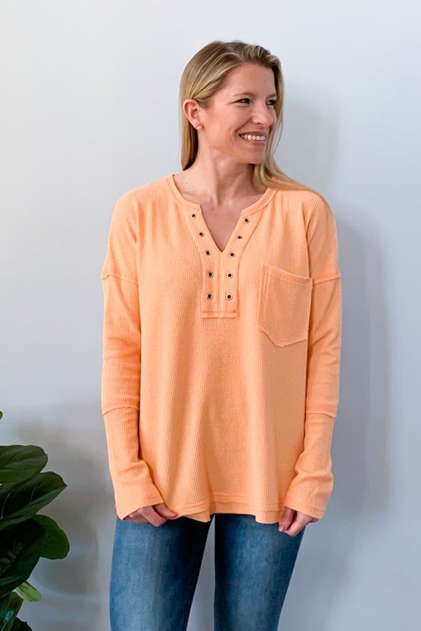 Whether your lounging or it's a casual day, you'll love our Waffle Knit Long Sleeve Top in Apricot  This super soft waffle knit top features long sleeves, split neckline with grommet detailing, and a front bust pocket.  Perfect for pairing with leggings and sneakers.  Details  Waffle Knit Long Sleeve SUPER soft Henley Style
