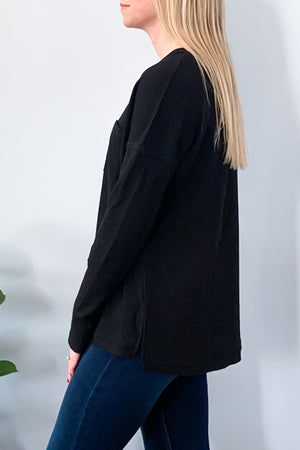 Our best selling waffle knit top is now available in Black.  Whether your lounging or it's a casual day, you'll love our Waffle Knit Long Sleeve Top in Black. This super soft waffle knit top features long sleeves, split neckline with grommet detailing, and a front bust pocket.  Perfect for pairing with leggings and sneakers.