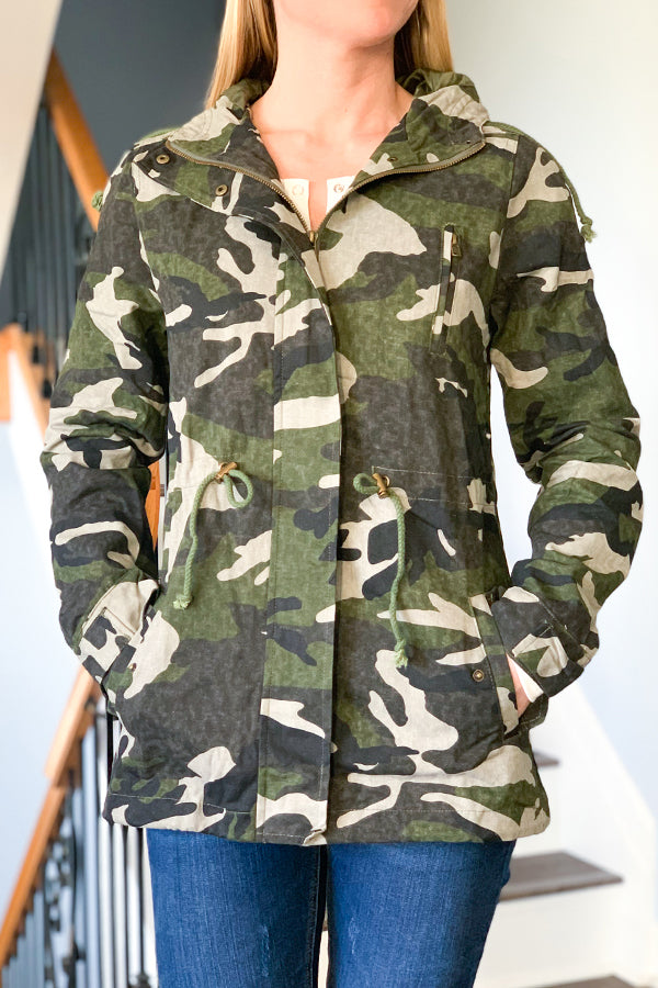 Fashion meets function with our Camo Utility Jacket With Hoodie.  This cutie features a drawstring detail at waist, side pockets, and zipper front with snap closure.  This utility jacket is lightweight and perfect for layering over a lightweight sweater or pairing with a basic tee for warmer days.  This will be your go-to jacket all season!