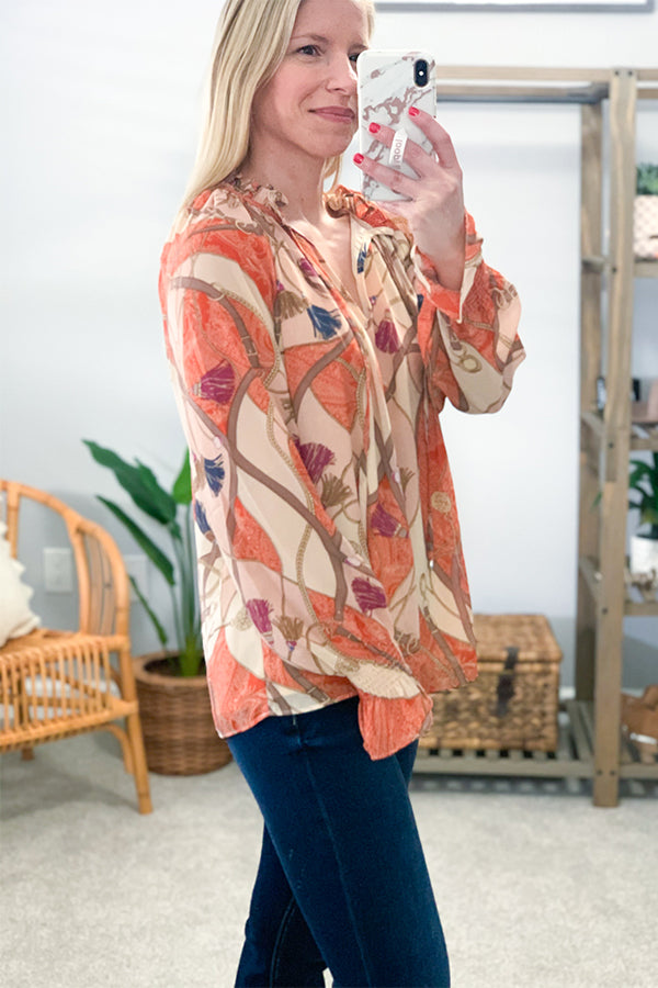 Feel chic in our Chain Print Balloon Sleeve Blouse.  Hues of orange, pink, salmon, and brown are printed on this relaxed blouse.  Featuring a split neckline, smocked elastic cuffs, and balloon sleeves.  This fun top has a necktie closure and sheer sleeves while the body is fully lined.  Pair with your favorite flares or skinny jeans to complete the look.