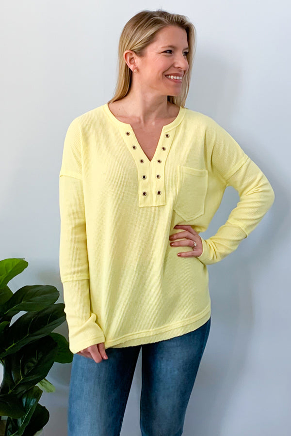 Add a touch of spring to your comfy, casual outfit with our Waffle Knit Long Sleeve Top in Neon Yellow. This super soft waffle knit top features long sleeves, split neckline with grommet detailing, and a front bust pocket.  Perfect for pairing with leggings and sneakers.  Details  Waffle Knit Long Sleeve SUPER soft Henley Style