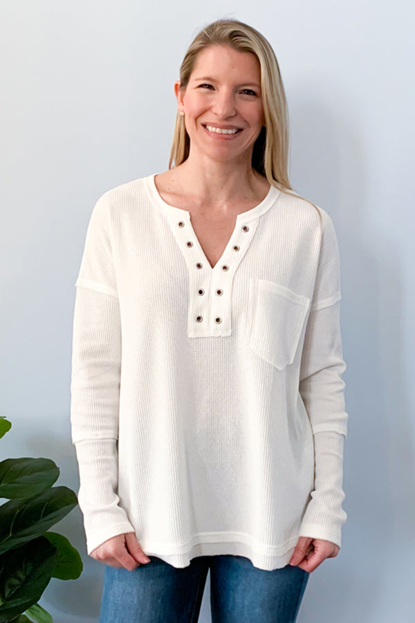 Look cute and feel comfy in our Waffle Knit Long Sleeve Top in Off White.  This super soft waffle knit top features long sleeves, split neckline with bronze grommet detailing, and a front bust pocket.  Perfect for pairing with leggings and sneakers.  Details  Waffle Knit Long Sleeve SUPER soft Henley Style