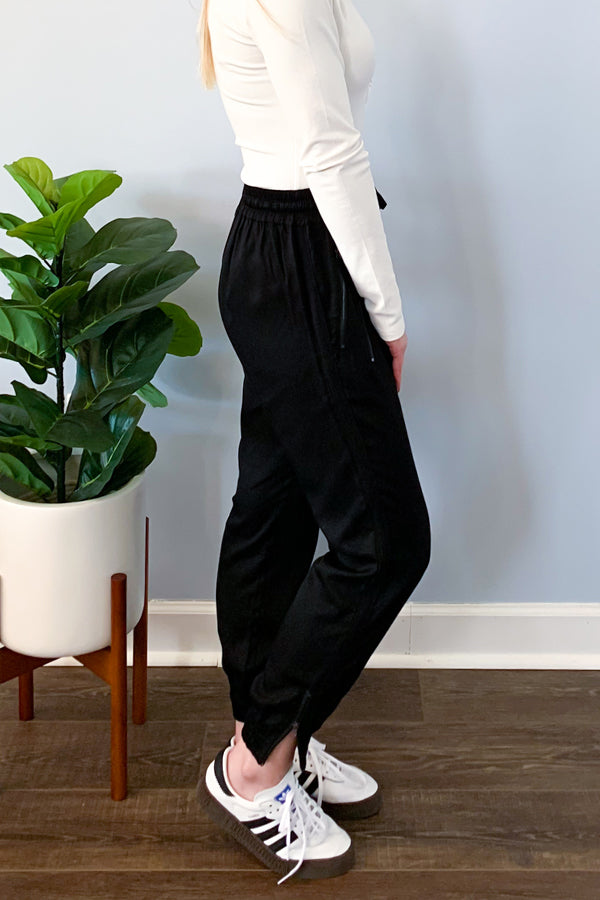 Our Black Tencel Utility Jogger Pants are a must-have for a casual style.  These tencel joggers features an elastic waistband with tie drawstring, functional zipper details on pockets, and functional zip ankle detail.  Pair with a henley bodysuit and sneakers to complete the look. We love how you can dress these up with heels or wear casual with sneakers.
