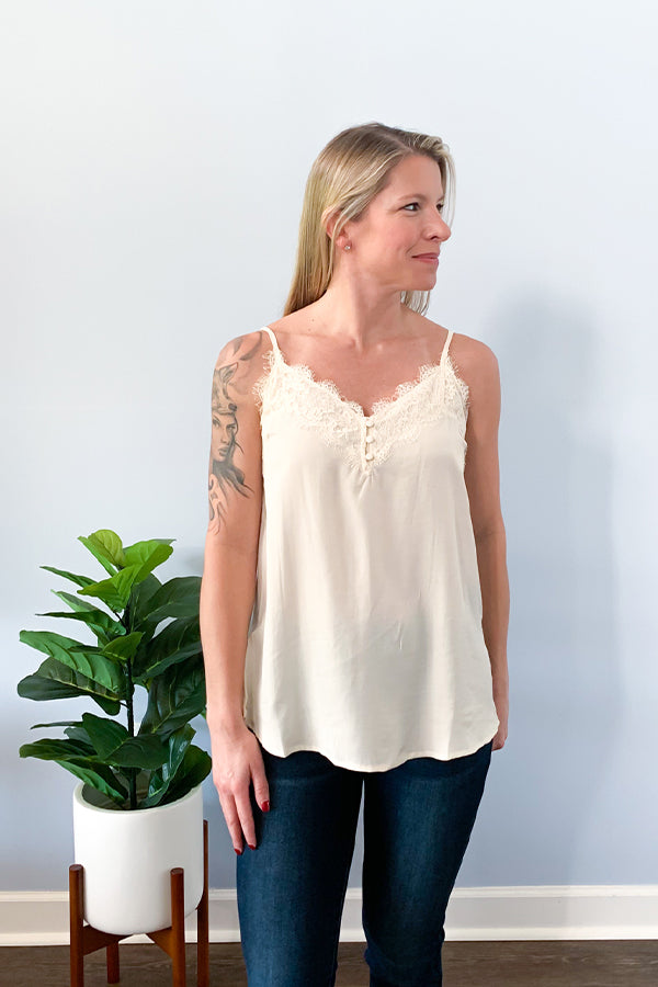 Our Ivory Lace Trim Button Up Cami Top is a closet-essential! Perfect for pairing underneath a cozy cardigan or chic blazer!  This dainty cami top features lace trim around the front and back, functional front buttons, and adjustable straps.  This cami is made with a lightweight fabric that is soft and has a satin feel to it.  Pair with your favorite cozy cardigan, jeans and booties for a cute outfit.  Change out your jeans with some leather leggings for a chic dinner outfit!