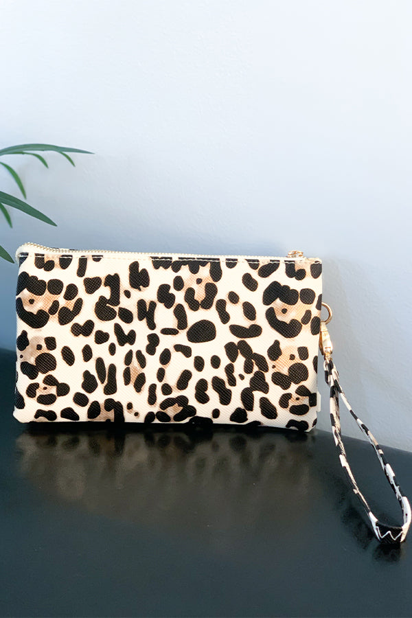 This crossbody bag is for all those cool cats and kittens out there! Our Ivory Leopard Crossbody Bag features a trendy leopard print in ivory, crossbody detachable strap, wristlet detachable strap, two small compartments inside with credit card slots, and a center zip compartment.  Perfect for throwing in a tote bag or wearing as is.