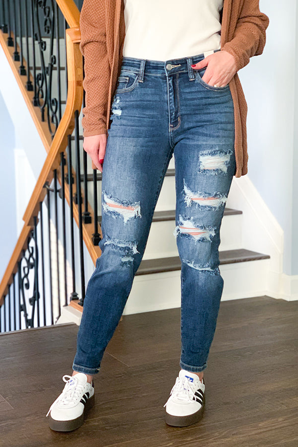 If you love distressed jeans as much as we do, then you'll love our Judy Blue Hi-Rise Distressed Boyfriend Jeans.  These high-waist jeans feature a boyfriend fit, classic 5-pocket detail, and trendy distressing.  These jeans are super comfy with a good amount of stretch.  They are a boyfriend fit. We recommend sizing down for a tighter fit.  Perfect for pairing with your favorite graphic tee, cardigan, and sneakers for a casual outfit.