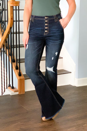 If loving flare jeans is wrong, then I don't want to be right! We are definitely in love with our KanCan High Rise Distressed Flare Dark Wash Jeans!  Minimal distressing, 5 button fly, and cute trouser style side pockets make these a must-have for any season! Perfect for pairing with wedges and a cute graphic tee!  These KanCan's run true to size.  If in between sizes, we recommend to size down if you want a tighter fit.