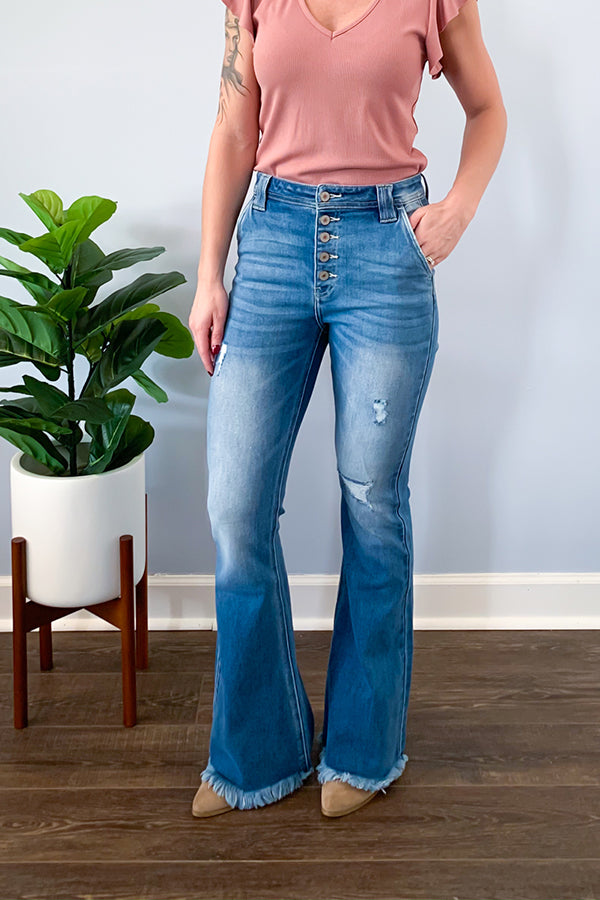"The cutest of the cutest are our KanCan High Rise Distressed Flare Light Wash Jeans! These stretchy high-rise jeans are slightly distressed with frayed hemlines.  Finished with button fly closure and trouser style pockets.  These flare jeans are a longer length with a 33.5"" inseam.  Perfect for pairing with a heeled boot for this season!"