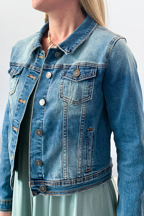 Everyone needs a closet staple like our KanCan Medium Wash Denim Jacket.  This medium wash jacket features a button front closure, two chest pockets and side pockets. and a light fade detail through the upper and lower half.  This jacket has stretch throughout the arms and back, making it comfortable to wear all day long.  This classic denim jacket will be your go-to jacket! Perfect for pairing over your favorite spring and summer dress or throw over a cute cami.