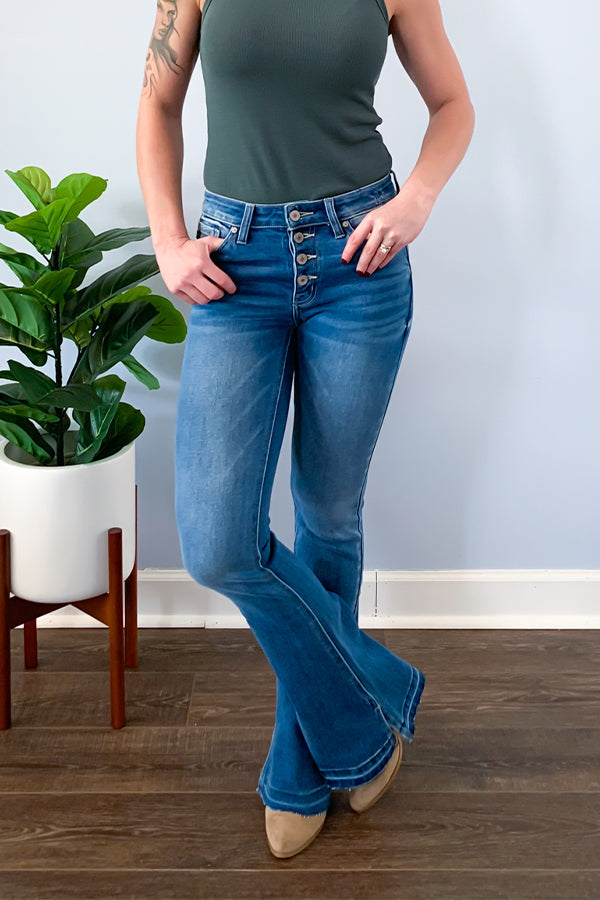 "The Mid Rise Button Front Flare Jeans With Side Slit by KanCan is the perfect flare for all year!  Featuring front button fly closure, frayed hems, and inner side slit detail.  These jeans are a must-have for this season! Pair with your favorite boots and a cute graphic tee!  These are true to size and are a longer length with a 33.5"" inseam."