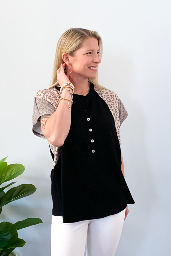 Show off your sass with our Leopard Mix Waffle Knit Short Sleeve Top in Black!  This henley style top features a round neckline with functional buttons, short sleeve, and color block animal print on the sleeves.  We love the lightweight waffle knit fabric of this top which makes it perfect for warmer days!  Pair with jeans and sneakers for the cutest outfit! Available in two colors. Entro Clothing.