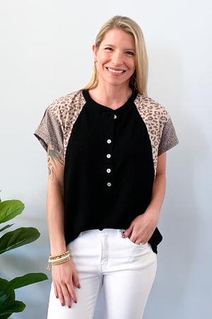 Show off your sass with our Leopard Mix Waffle Knit Short Sleeve Top in Black!  This henley style top features a round neckline with functional buttons, short sleeve, and color block animal print on the sleeves.  We love the lightweight waffle knit fabric of this top which makes it perfect for warmer days!  Pair with jeans and sneakers for the cutest outfit! Available in two colors.