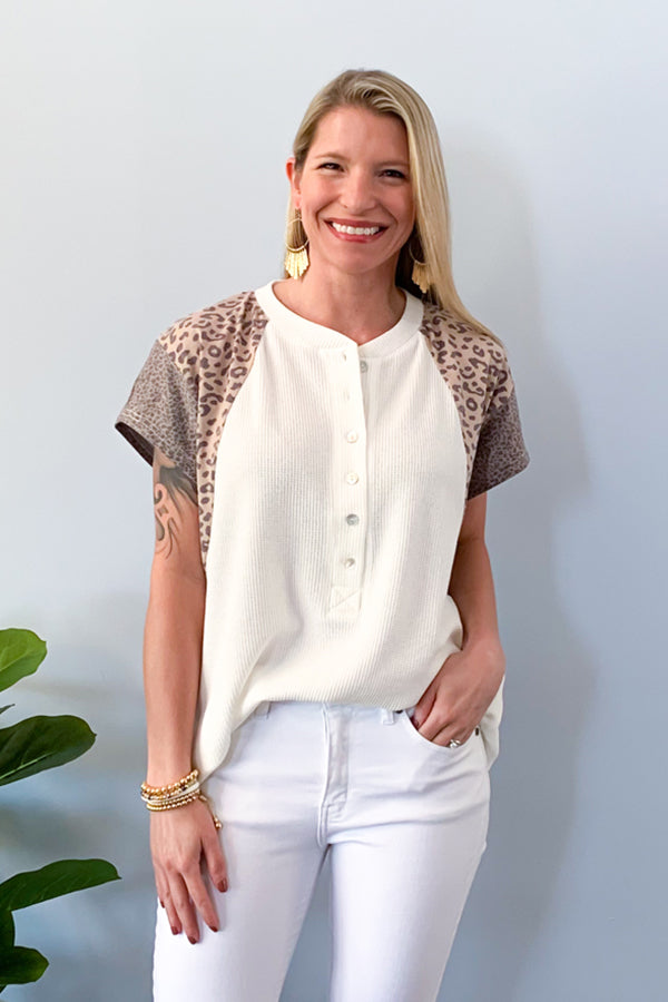 Show off your sass with our Leopard Mix Waffle Knit Short Sleeve Top in Off White!  This henley style top features a round neckline with functional buttons, short sleeve, and color block animal print on the sleeves.  We love the lightweight waffle knit fabric of this top which makes it perfect for warmer days!  Pair with jeans and sneakers for the cutest outfit! Available in two colors. Entro Clothing.