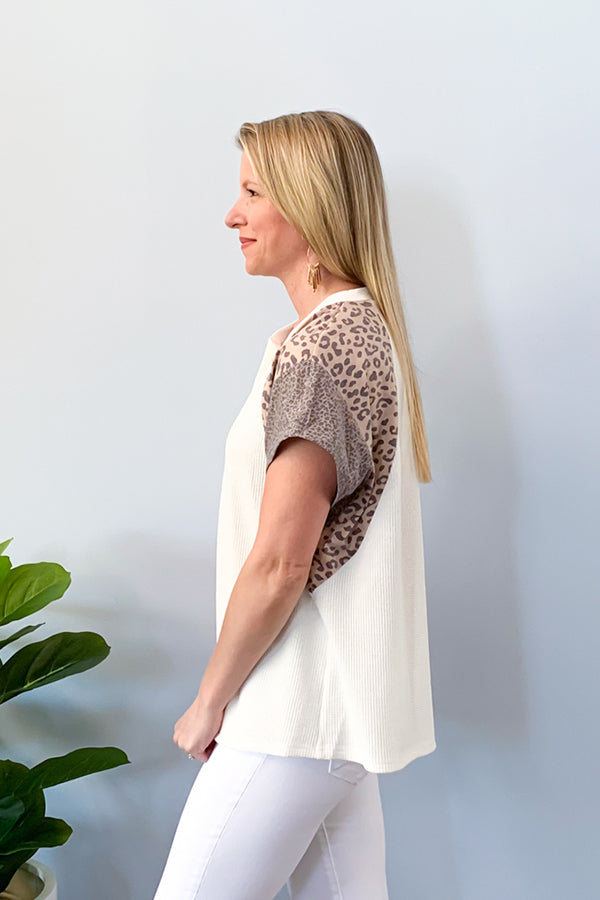 Show off your sass with our Leopard Mix Waffle Knit Short Sleeve Top in Off White!  This henley style top features a round neckline with functional buttons, short sleeve, and color block animal print on the sleeves.  We love the lightweight waffle knit fabric of this top which makes it perfect for warmer days!  Pair with jeans and sneakers for the cutest outfit! Available in two colors.