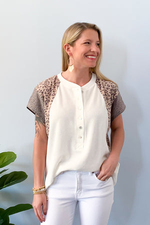 Show off your sass with our Leopard Mix Waffle Knit Short Sleeve Top in Off White!  This henley style top features a round neckline with functional buttons, short sleeve, and color block animal print on the sleeves.  We love the lightweight waffle knit fabric of this top which makes it perfect for warmer days!  Pair with jeans and sneakers for the cutest outfit! Available in two colors. Entro Tops.