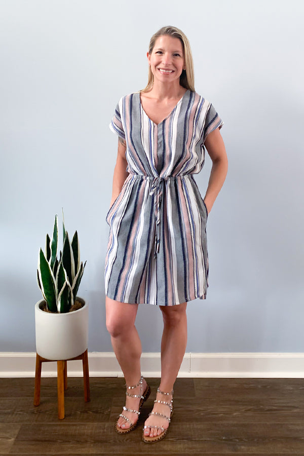 A striped summer dress perfect for work to weekend.  The Striped Summer Dress With Pockets is just that!  This beautiful pink, blue, white, and grey striped dress features a cinched waist, tie front, and side pockets.  Perfect for pairing with sneakers for a fun weekend outfit or pairing with wedge sandals and a denim jacket for a work outfit.