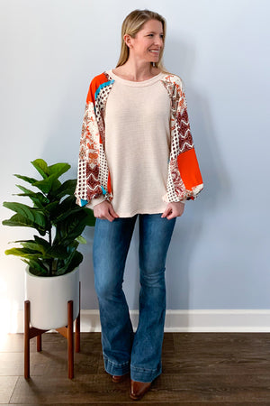 A classic waffle knit top with cute contrasting sleeves!  Our Waffle Knit Top With Contrast Sleeves is a cream base with a hint of blush and the cutest patchwork bubble sleeves.  We are loving the pop of color these sleeves have with turquois and a blood orange colors!  You'll love the boho vibes of this top!  Pair with your favorite flares or skinny jeans to complete the look.