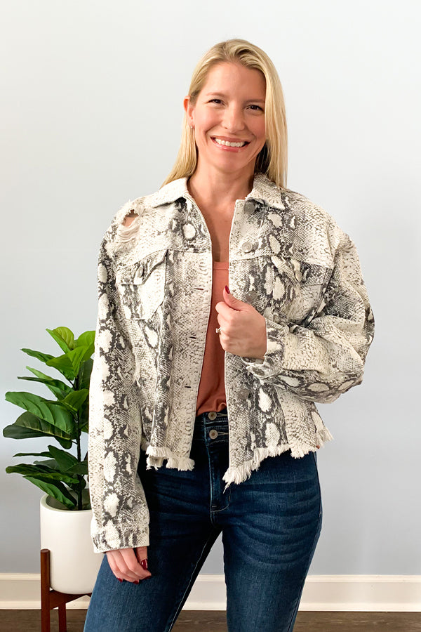 Can't get enough of animal prints? Then you'll love our Snakeskin Denim Jacket!  We sure do!! Trendy snakeskin print jacket featuring a relaxed fit, distressed detail throughout, and raw edge front hem.  This denim jacket has a button down closure and button cuff closure.  Pair perfectly with jeans for an edgy, but cute, outfit!
