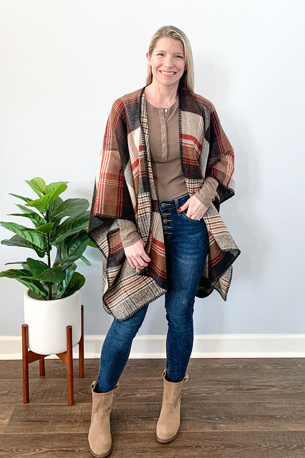 Our Reversible Plaid Ruana Poncho will keep you warm and cozy on those chilly nights.  The open front design makes this an easy piece to throw over your favorite long sleeve tee and jeans, while the relaxed fit makes it so comfy! This reversible ruana is a mixture of ivory, mocha, mustard, rust, and black.