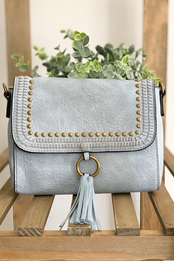 It's all about the simple, chic details with our Light Blue Crossbody With Grommet And Tassel Details.  This crossbody is a beautiful light blue with stud detailing and fun tassel front with a snap closure and zipper closure.
