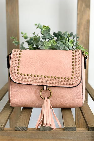 It's all about the simple, chic details with our Light Pink Crossbody With Grommet And Tassel Details.  This crossbody is a beautiful light blue with stud detailing and fun tassel front with a snap closure and zipper closure.