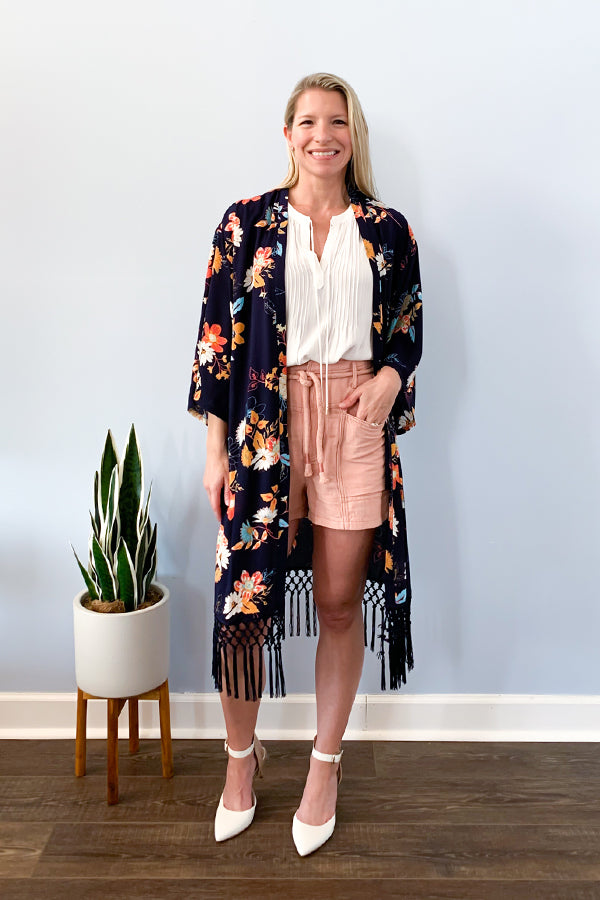 The perfect kimono for any occasion!  The Floral Print Kimono With Fringe Bottom features a beautiful floral pattern, loose fit, and fringe bottom detail.  This kimono is perfect for achieving an effortless look with just throwing over a tee and shorts.  Dress it up by pairing with a cami, skinny jeans, and heels.