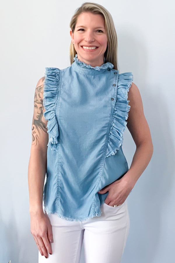 The Elan Sleeveless Ruffle Denim Top features raw hem ruffles on the front and back with a ruffle neck detail with button closure.  Perfect for spring and summer, this sleeveless top is finished with a shirt tail bottom and side vents. This chambray top will go perfect with your favorite colored jeans.
