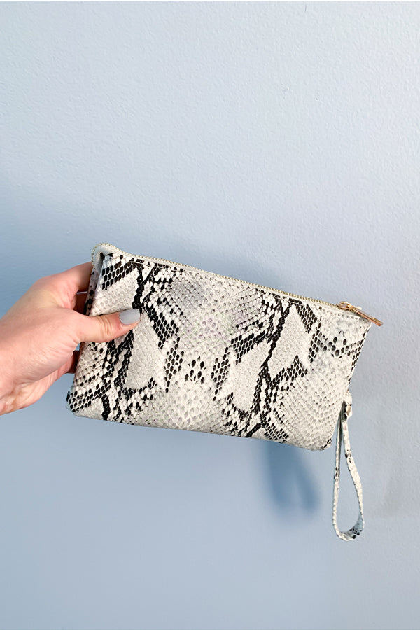 We're loving the Snake Gray Stone Crossbody Bag.  This handbag features the most beautiful, luxurious materials!  Features include a crossbody strap, wristlet straps, two large pockets with two small compartments within that, and a center zip compartment.  The two smaller compartments include credit card slots.  Perfect for throwing in your tote bag and pulling it out when you're on the go.