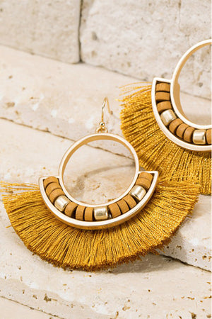 "Add a fun touch of mustard to any outfit with these tassel and wood bead earrings.  Gorgeous metal ring and fine thread tassel  finished with wood bead accent.  Approximately length is 2"" and width is 2 1/4"" Nickle/lead compliant"