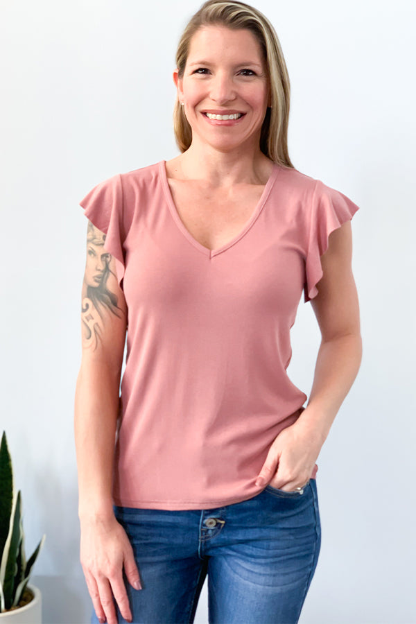 The Blush Ruffle Sleeve V Neck Top is perfect for achieving an effortless style.  This pretty blush top features flutter cap sleeve detail, v-neckline, and is made with soft, stretchy fabric.  Perfect to pair with jeans or shorts for a casual outfit.  This top is also great for layering under a kimono or a denim jacket. Velvet Heart.
