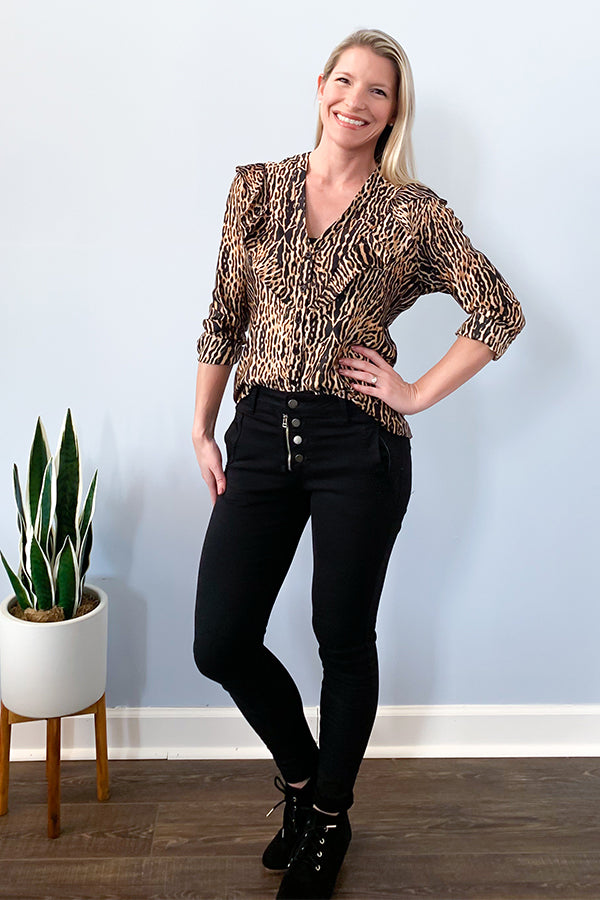 Veronica M The Animal Print Long Sleeve Ruffle Blouse features a black base with brown and gold tone animal inspired print.  Flattering v-neckline with ruffle details give this button up blouse a unique look.  Made with a soft, satin-like material.  The elastic cuffs make it easy to wear as a 3/4 sleeve style or long sleeve style.  This high-quality blouse is perfect for adding a pop of style to your work outfit.  Pair with some black skinny jeans and cute booties for a night-out outfit.