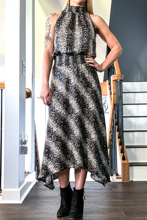 Veronica M Snake Print Satin Hi-Neck Smocked Maxi Dress Smocked hi-neckline Keyhole and button at back neckline Smoked waistband Lined skirt Not sheer Uneven hem detail Snake print Colors: Black, grey, and white Satin-like fabric Woven, non-stretch fabric 100% Polyester Machine wash Made in U.S.A.