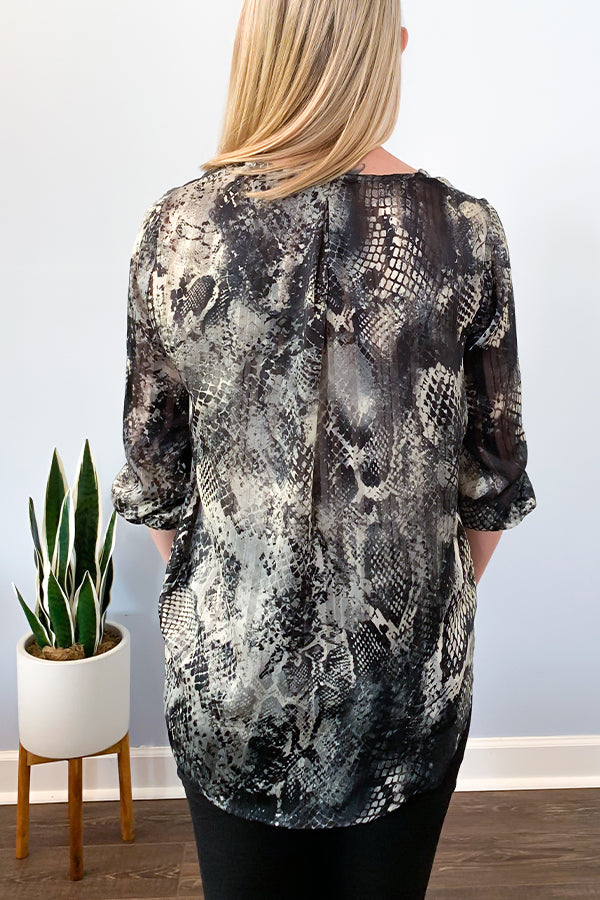 Veronica M The Snake Print Surplice Blouse features a v-neckline, high-low hem, relaxed fit, and 3/4 sleeve.  Beautiful soft, semi sheer fabric includes colors of black, grey, and hints of gold through out.  An easy top to dress up with black denim and heels or wear to work with dress pants and a blazer.  Veronica M Clothing