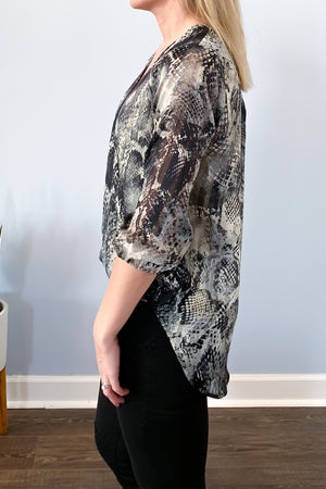 Veronica M The Snake Print Surplice Blouse features a v-neckline, high-low hem, relaxed fit, and 3/4 sleeve.  Beautiful soft, semi sheer fabric includes colors of black, grey, and hints of gold through out.  An easy top to dress up with black denim and heels or wear to work with dress pants and a blazer.  Veronica M Clothing.