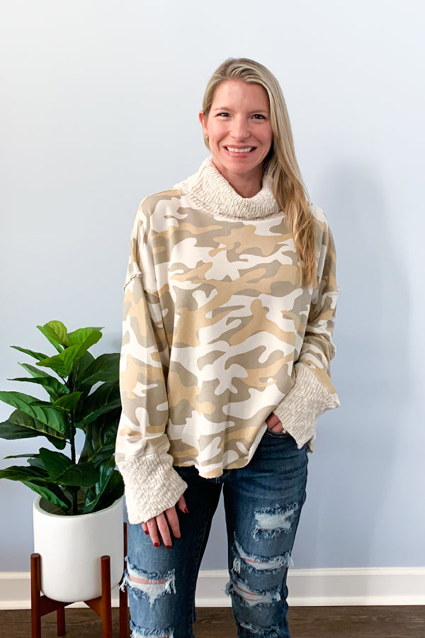 Stay cozy and on trend with our Vintage Havana Camo Print Cowl Neck Sweater.  This cute cowl neck sweater features an all over camo print in a neutral color that looks so cute with jeans.  Finished with contrast, cozy, knit sleeves, knit neckline, and raw edge hemline.  Pair with distressed jeans for a casual look.