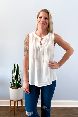 The White Sleeveless Top With Pleated Neckline is a must-have! Beautiful pleated detail give this sleeveless top a delicate touch.  Complete with a cute neck tie closure.  This top is lightweight and perfect for summer.  Pair with cute shorts and sandals for a daytime outfit.  Pair under a blazer for a chic office look....or zoom call! Skies are blue clothing.