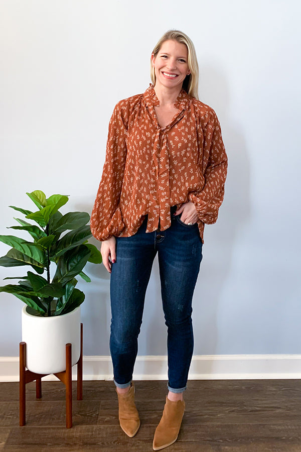 Our Floral Tie Neck Blouse In Rust features a cute, fall floral print in ivory on a beautiful rust base. A v-neckline, ruffle mock neck with tie, balloon sleeves, and slightly pleated fabric add cute details to this relaxed fit blouse. Perfect for the office or a cute date night outfit.